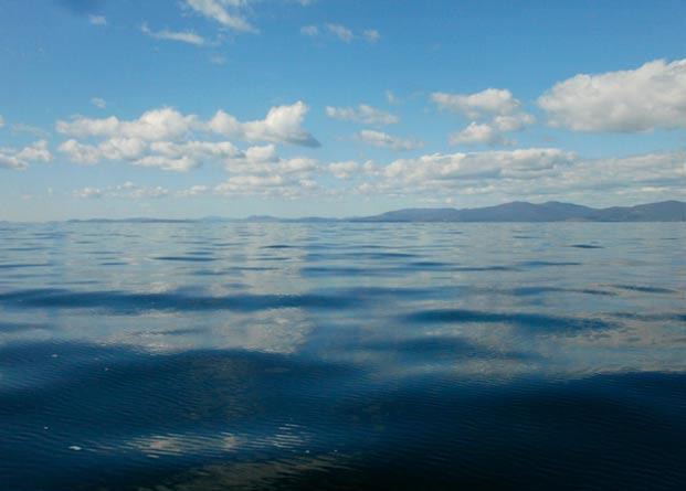 Облака отражаются в бледно-голубой воде